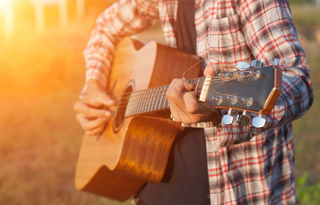 Hand of man playing guitar in outdoor,soft focus. Stock Photo