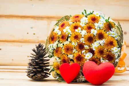 Two heart and flower bouquet on wooden table background,soft focus.