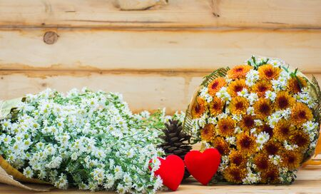 Flower bouquet and two heart on wooden table background,soft focus. Imagens