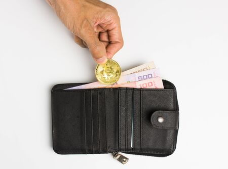 Hand holding bitcoin in wallet on white background,selective focus. Foto de archivo