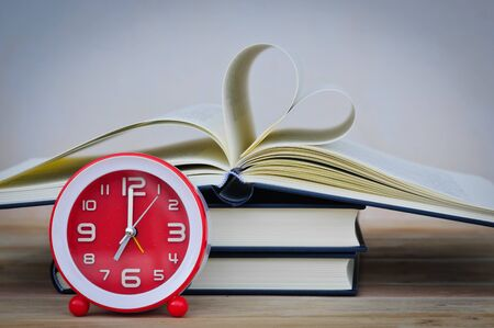 Old book and clock on wooden table,soft focus. Stockfoto