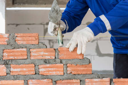 Worker installing brick for wall in construction,selective focus.