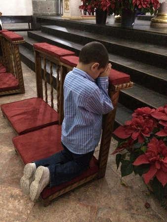 Young boy praying in church