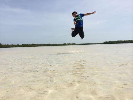 boy jumping in the beach Stock fotó