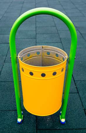 papelera de reciclaje: Papelera de reciclaje amarillo en un parque infantil. Foto de archivo