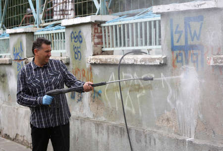 Sofia, Bulgaria - September 12, 2014: A cleaner is cleaning graffiti from the outer side of a wall of a school in Sofia.