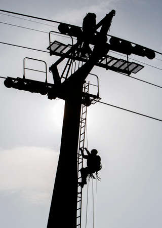 carrying the cross: Silhouetee of a person climbing a cabin lift pillar.