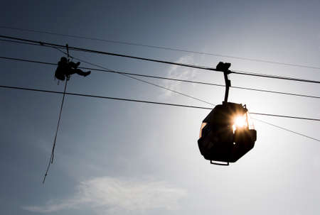 Silhouetee of a cabin ski lift and rescuer. photo