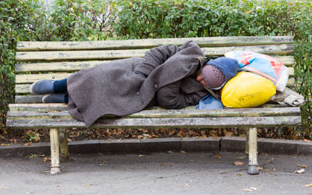 Sofia, Bulgaria - November 4, 2014: Homeless man is sleeping on a bench in the center of Sofia. Years after joining the EU Bulgaria is still the poorest country in the union. Stock Photo - 33913496