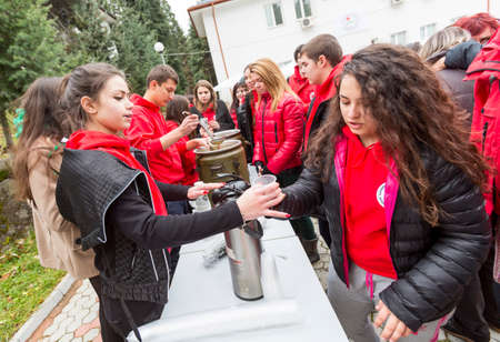 detriment: Sofia, Bulgaria - December 5, 2014: Members from Bulgarian Red Cross Youth (BRCY) voluntary youth organization are giving coffee, tea and soup to other members as participating in a training simulation of a natural disaster situation.