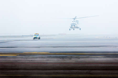 landing strip: Helicopter on a foggy landing strip led by a car.