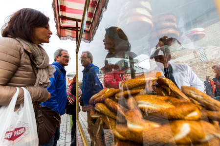 turkish ethnicity: Istanbul, Turkey - November 14, 2014: Tourists are buying pretzels in the center of Istanbul.