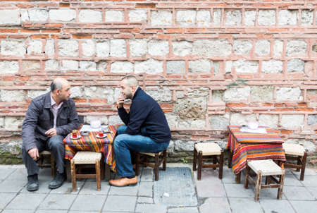social grace: Istanbul, Turkey - November 15, 2014: Two Turkish men are drinking tea outside of a cafe at a market street in Istanbul. Editorial