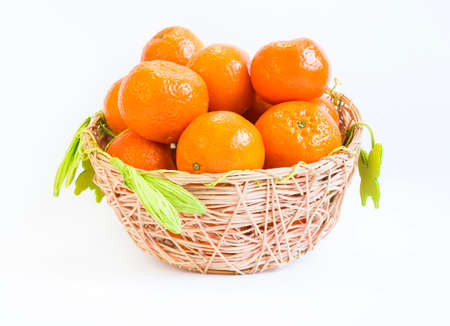 bisected: Tangerine in a basket isolated on a white background. Stock Photo