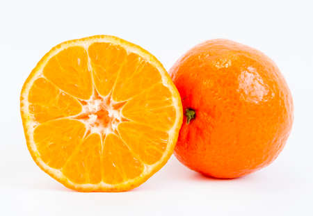 food staple: One half of a tangerine slice and a whole mandarin isolated on a white background.