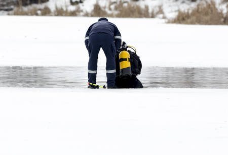 dry suit: A diver is preparing before getting into the frozen lake waters before Bulgarian men jump for a wooden cross at Epiphany day celebration in Sofia.