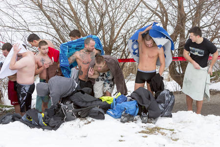 get dressed: Sofia, Bulgaria - January 6, 2015: Men are getting dressed after jumping into the frozen lake waters for a wooden cross at Epiphany day celebration in Bulgaria.
