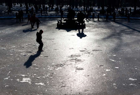 peacefull: Children are playing on the surface of a frozen fountain. Stock Photo