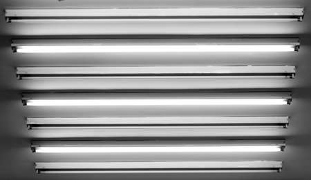 household fixture: Fluorescent lamps on the ceiling. Half of them lit. Stock Photo