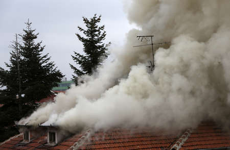 trees services: A house roof on fire and smoke.