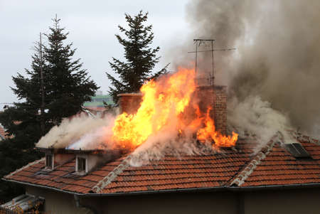 A house roof on fire and smoke.