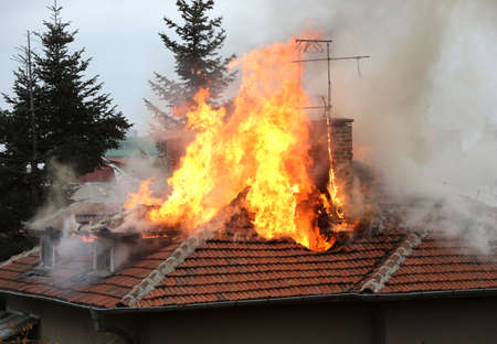 fire damage: A house roof on fire and smoke.
