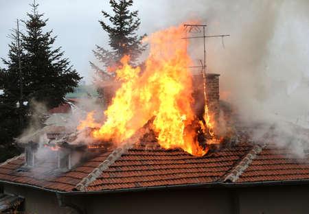Een huis dak in brand en rook. Stockfoto