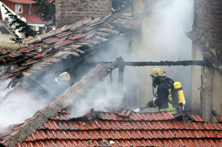 Firefighters on a burning house roof.