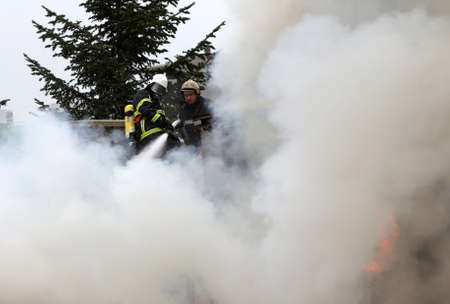 burning house: Sofia, Bulgaria - November 24, 2012: Firefighters are extinguishing fire on a burning house roof.