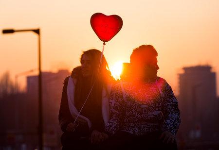 silhouettes lovers: Sofia, Bulgaria - 14 de febrero de 2015: Una silueta de una joven pareja en el amor con un globo rojo forma de coraz�n que se sienta en un puente en la noche del D�a de San Valent�n.