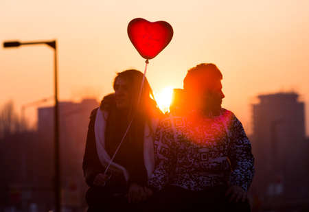 teenage love: Sofia, Bulgaria - February 14, 2015: A silhouette of an young couple in love with a red heart shape balloon sitting on a bridge at the night of Valentines Day. Editorial