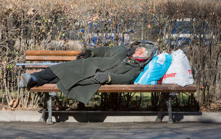 Sofia, Bulgaria - February 26, 2015: Homeless woman is sleeping on a bench in the park next to the parliament in Sofia, Bulgaria. Years after joining the EU Bulgaria is still the poorest country in the union. Editorial
