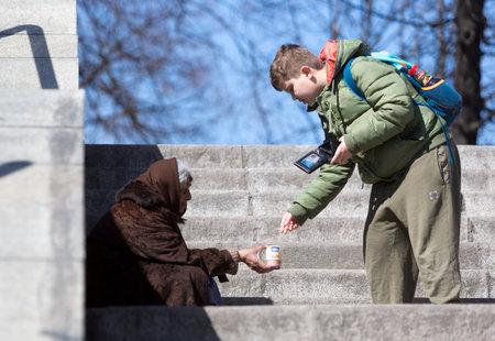 niños pobres: Sofia, Bulgaria - 17 de marzo de 2015: Un muchacho está dando dinero a un mendigo mujer sin hogar que está pidiendo a las escaleras paso inferior de metro en el centro de Sofía.