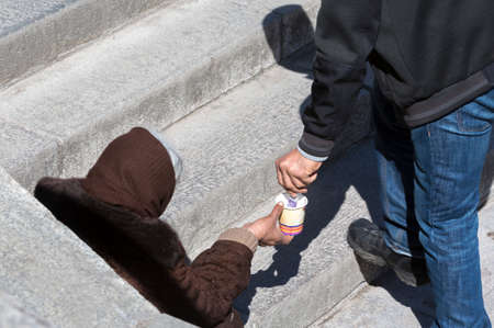 hombre pobre: Un hombre le está dando dinero a un mendigo mujer sin hogar que está pidiendo a las escaleras paso inferior de metro en el centro de Sofía.