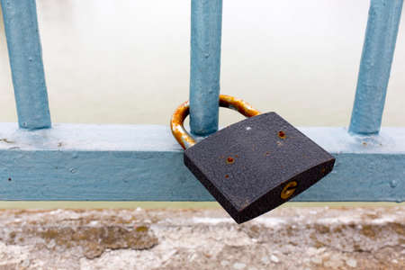jailed: A lock on a fence colored in blue.