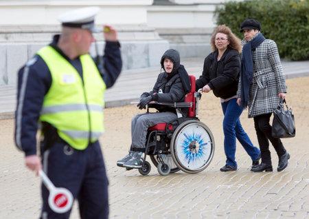 ni�o discapacitado: Sofia, Bulgaria - 03 de abril 2015: Una madre y su hijo van a una protesta con otros padres y familiares de ni�os con discapacidad f�sica y adultos contra las leyes estatales que se considerar� si discriminatorias.