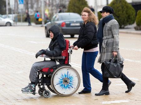 niños discapacitados: Sofia, Bulgaria - 03 de abril 2015: Una madre y su hijo van a una protesta con otros padres y familiares de niños con discapacidad física y adultos contra las leyes estatales que se considerará si discriminatorias.