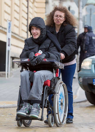 paralysis: Sofia, Bulgaria - April 3, 2015: A mother and her son are going to a protest with other parents and relatives of physically disabled children and adults against state laws which they considere discriminatory. Editorial