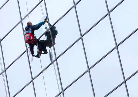 sanitation: Sofia, Bulgaria - April 7, 2015: Sanitation worker are cleaning the glass facade of a hotel in the center of Sofia.