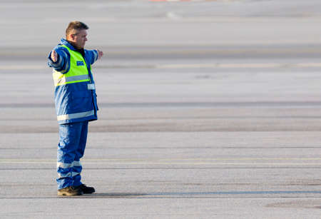navigating: Sofia, Bulgaria - April 11, 2015: An airport worker is navigating the movement of an airplane on the airport runway after landing.