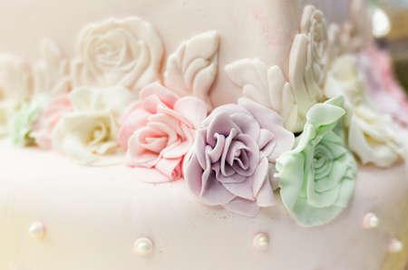 eating cake: Diferent handmade colourful sugar roses on a wedding cake. Stock Photo
