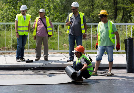 waterproofing: Sofia, Bulgaria - May 21, 2015: Construction workers are waterproofing a bridge surface floor at a highway in Sofia.