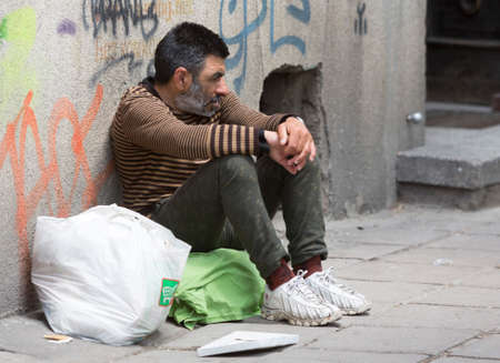 homelessness: Skopje, Macedonia - May 14, 2015: A homeless beggar is begging on a busy street in the center of Skopje. Macedonia is still one of the poorest countries in the Balkans years after the collapse of the Soviet Union.