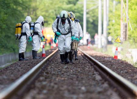 Een team werken met giftige zuren en chemicaliën is het naderen van een chemische lading treinongeluk in de buurt van Sofia, Bulgarije. Teams uit Brandweer deelnemen in een noodsituatie training met gemorst giftige en brandbare materialen. Stockfoto - 40368415