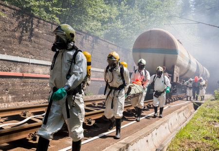 bombero: Sof�a, Bulgaria - 19 de mayo 2015: Un equipo que trabaja con �cidos t�xicos y productos qu�micos est� salvando a gente de un choque de trenes de carga qu�mica. Los equipos de bomberos est�n participando en un entrenamiento de emergencia con materiales t�xicos e inflamables derramados.