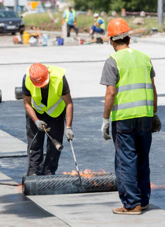 waterproofing material: Construction workers are waterproofing a bridge surface floor at a highway in Sofia.