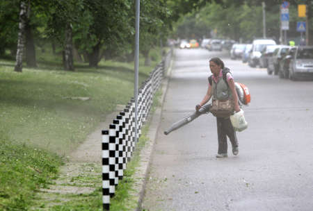 pressured: Skopje, Macedonia - May 14, 2015: A woman is cleaning cut grass from a footpath in a park with a pressured air machine.
