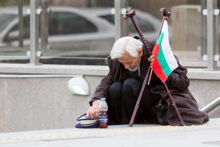 dirty old man: Sofia, Bulgaria - May 15, 2015: A homeless beggar is begging at a subway underpass entrance in the center of Sofia. Years after joining the EU Bulgaria is still struggling with increasing poverty among its population. Editorial