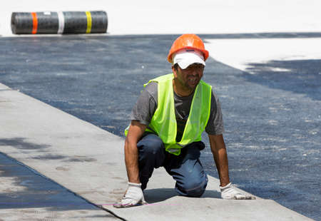waterproofing material: Sofia, Bulgaria - May 21, 2015: Construction workers are waterproofing a bridge surface floor at a highway in Sofia.