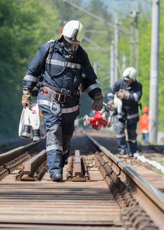 flammable: Firefighters are approaching a chemical cargo train crash near Sofia, Bulgaria. Teams from Fire department are participating in an emergency training with spilled toxic and flammable materials. Stock Photo